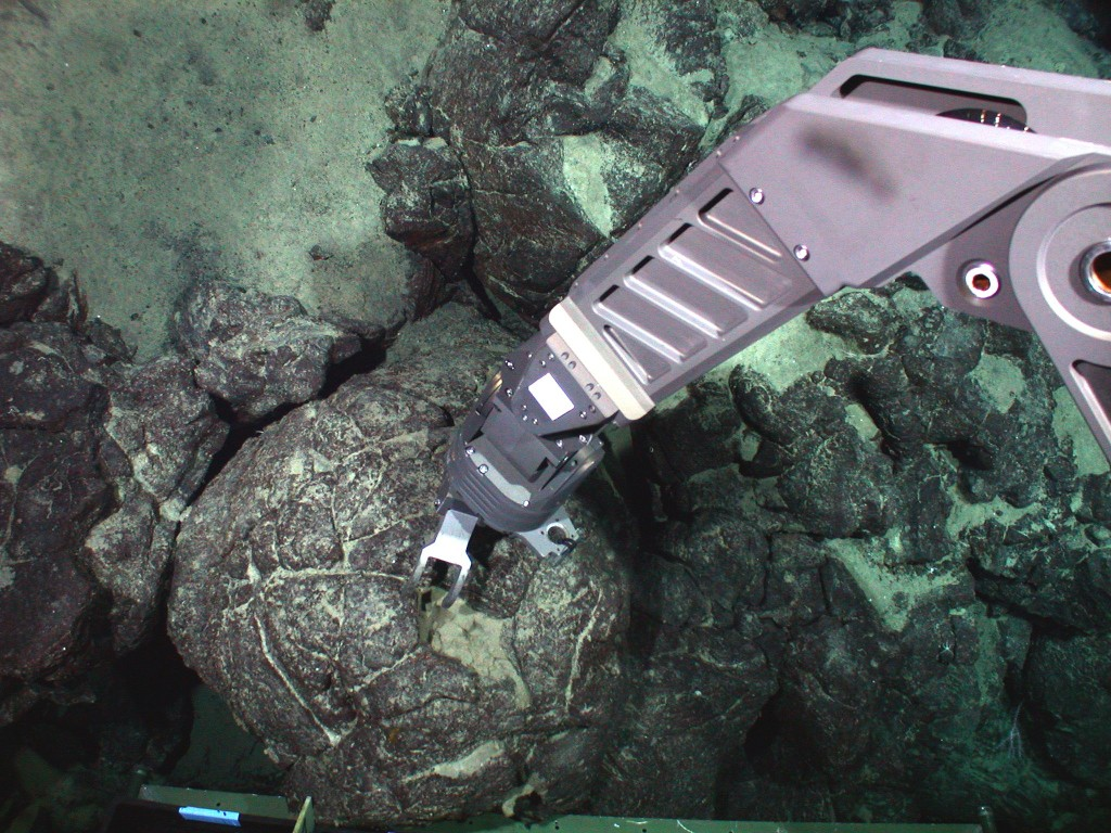 Underwater action scene of robotic mechanical arm on the JASON2 submersible collecting a pillow lava sample from Mauna Loa volcano at 10,000 feet below sea level during a 2002 expedition.  Photo taken by camera on JASON2 (Credit: M. Garcia and J.M. Rhodes)